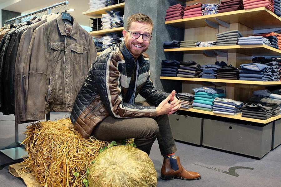 Männliches Model mit einer stylischen Lederjacke von Milestone, Rolli von Digel, mit Hose von Pierre Cardin und Boots von Lloyd. sitzt auf einem Strohballen im Omega Männermoden Geschäft.