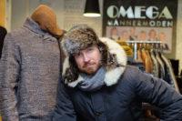 Männliches Model mit einem warmen Parka von Wellensteyn, mit Mütze und Schal von Ragman